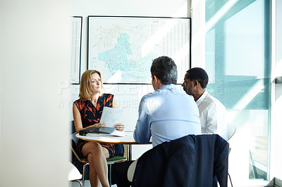 Buy stock photo Shot of three businesspeople meeting in the boardroom