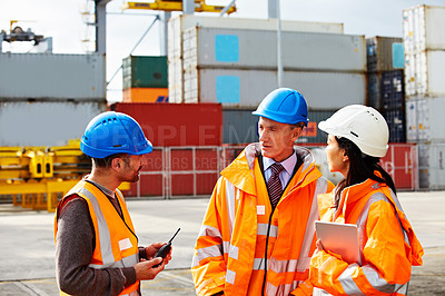 Buy stock photo Shot of three workers talking while standing on a commercial dock