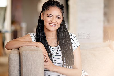Buy stock photo Shot of an attractive young woman relaxing on her home sofa