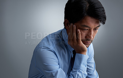 Buy stock photo Studio shot of a businessman looking despondent against a gray background