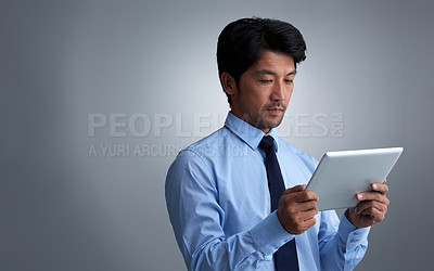 Buy stock photo Studio shot of a businessman using a digital tablet against a gray background