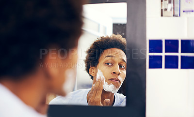 Buy stock photo Shot of a young man applying shaving cream to his face in the bathroom