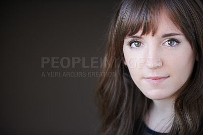 Buy stock photo Portrait of a beautiful young woman posing against a dark background