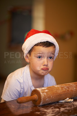 Buy stock photo Shot of a playful little boy baking at home during Christmas