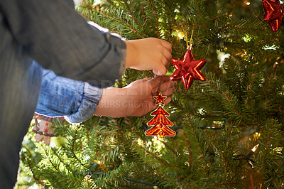 Buy stock photo Cropped shot of a child decorating a Christmas tree at home