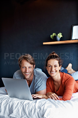 Buy stock photo Portrait of a smiling mature couple lying on their bed using a laptop