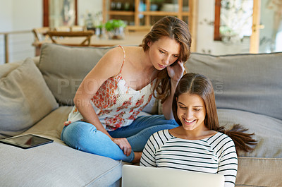 Buy stock photo Shot of two young friends sitting in the living room using a laptop together