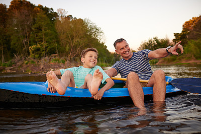 Buy stock photo Shot of a father and son sitting in a rowboat together on a lake