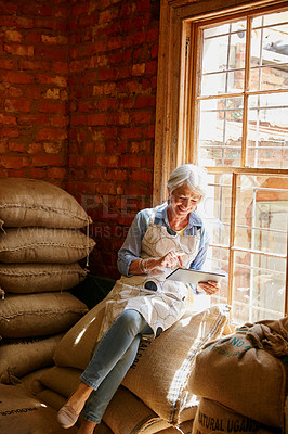 Buy stock photo Cropped shot of a senior woman using a tablet while working in a roastery