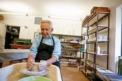 Buy stock photo Shot of a senior man making a ceramic pot in a workshop