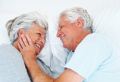 Buy stock photo Closeup of senior couple lying in bed and smiling with man touching woman's face