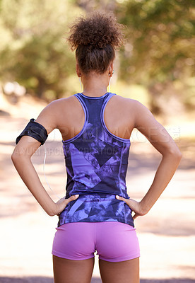 Buy stock photo Rearview of a sporty young woman out for a run