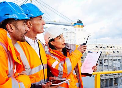 Buy stock photo Shot of three workers talking together while working on a commercial dock