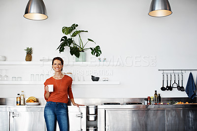 Buy stock photo Portrait of a smiling mature woman standing in her kitchen drinking coffee