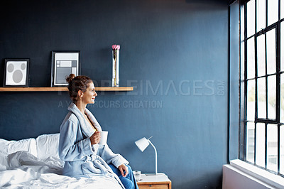 Buy stock photo Shot of a mature woman sitting on her bed drinking a coffee