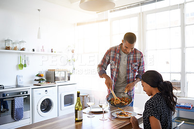 Buy stock photo Shot of a young couple eating dinner in their kitchen