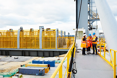 Buy stock photo Shot of three workers talking together while standing on an overhead walkway on a commercial dock