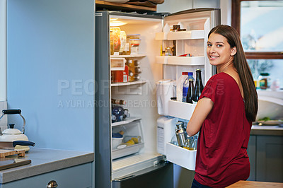 Buy stock photo Portrait of a young woman standing by an open fridge in her kitchen