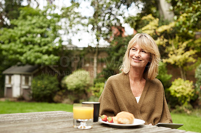Buy stock photo Shot of a mature woman sitting in her yard eating breakfast