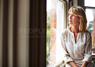 Buy stock photo Shot of a mature woman sitting by a window at home