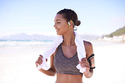 Buy stock photo Shot of a fit young woman taking a break from her workout at the beach