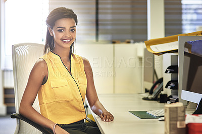 Buy stock photo Portrait of a smiling young woman working at her desk in an office