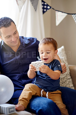 Buy stock photo Shot of an adorable little boy opening presents with his father on his first birthday