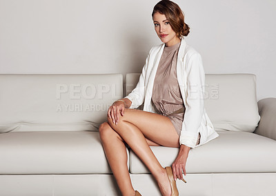 Buy stock photo Shot of a young woman sitting on her living room sofa