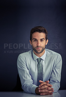 Buy stock photo Portrait of a young corporate businessman sitting at a desk against a dark background