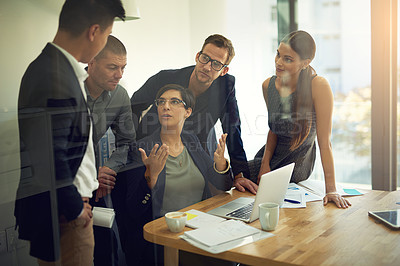 Buy stock photo Shot of a group of coworkers discussing something on a laptop during a meeting