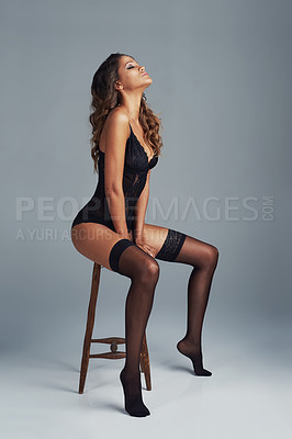 Buy stock photo Shot of a young woman wearing a body suit  on a stool against a grey background