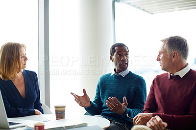 Buy stock photo Shot of three colleagues having a meeting in an office