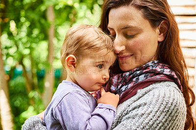 Buy stock photo Shot of a mother holding her baby girl in her arms outside