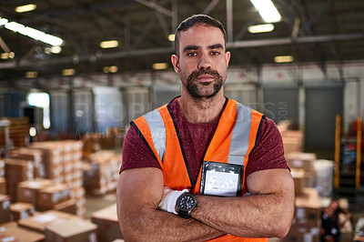 Buy stock photo Portrait of a worker standing with his arms crossed in a large warehouse full of boxes