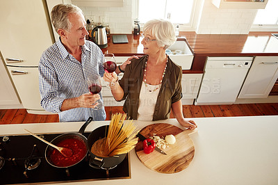 Buy stock photo Shot of a senior couple enjoying a glass of wine while cooking supper