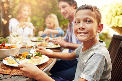 Buy stock photo Portrait of a happy little boy enjoying an outdoor lunch with his family