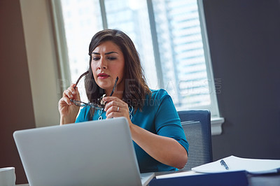 Buy stock photo Shot of a frowning businesswoman putting on her glasses to look at something on her laptop