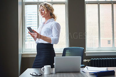 Buy stock photo Shot of a businesswoman using a phone in an office