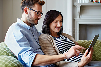 Buy stock photo Shot of a pregnant woman and her husband using a digital tablet while sitting on their sofa
