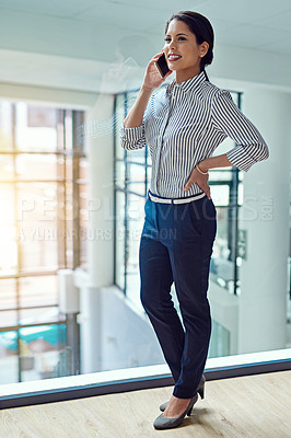 Buy stock photo Shot of a young businesswoman talking on a cellphone in an office