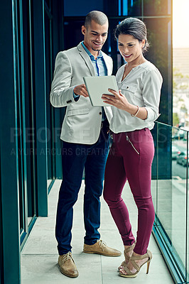 Buy stock photo Shot of two young coworkers using a digital tablet together at work