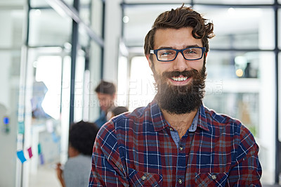 Buy stock photo Portrait of a young businessman standing in an office with colleagues in the background