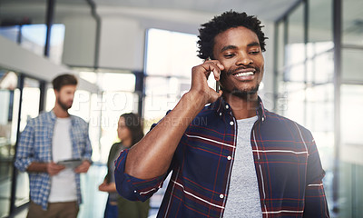 Buy stock photo Cropped shot of a young designer talking on a cellphone in an office with colleagues in the background