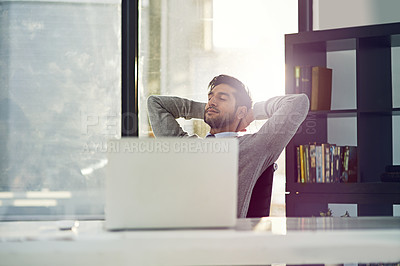 Buy stock photo Cropped shot of a young businessman sitting with his hands behind his head at his desk