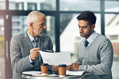 Buy stock photo Cropped shot of two businessmen looking over some paperwork in the office