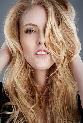 Buy stock photo Studio portrait of an attractive young woman feeling her beautiful long blonde hair against a gray background