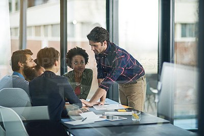 Buy stock photo Shot of a creative businessman leading his colleagues in a meeting