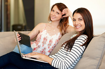 Buy stock photo Shot of two young friends sitting on the sofa using a laptop and digital tablet