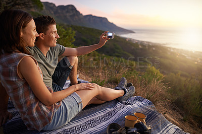 Buy stock photo Shot of a happy young couple taking a selfie on their date outdoors