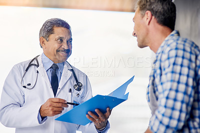 Buy stock photo Shot of a mature doctor giving his patient feedback during a consult